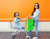 Lycklig familjmoder och barn med spårvagnvagns- och shoppingpåsar Arkivfoto