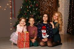 Lycklig familjmoder och barn på jul på julgranen med gåvor royaltyfri fotografi