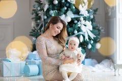 Lycklig familjmoder och barndotter på julmorgon på julgranen med gåvor royaltyfri foto