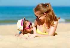 Lycklig familjmoder och barndotter på stranden i sommar arkivfoto