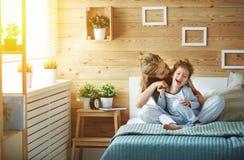 Lycklig familjmoder och barndotter som skrattar i säng Arkivfoton