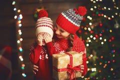 Lycklig familjmoder och barnflicka med julklapp Arkivfoto
