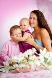 Lycklig familjmoder och hennes barn pojke och flicka som inomhus sitter Royaltyfri Fotografi