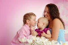 Lycklig familjmoder och hennes barn pojke och flicka som inomhus sitter Arkivbild