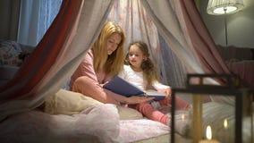 Lycklig familjmoder och hennes liten dotter som hemma läser en bok i ett tält stock video
