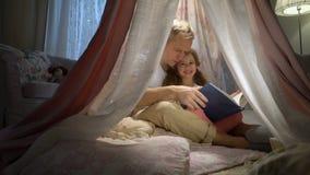 Lycklig familjmoder och hennes liten dotter som hemma läser en bok i ett tält arkivfilmer