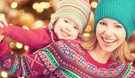 Lycklig familjmoder och liten dotter som spelar i vintern för jul