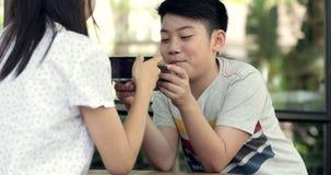 Lycklig familjmoder och son som tillsammans spelar leken på den mobila mobiltelefonen