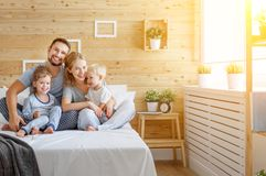 Lycklig familjmoderfader och barn dotter och son i säng Fotografering för Bildbyråer