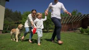 Lycklig familjmoderfader och son med hundkapplöpninghusdjur att köra ändå gården Handheld skott stock video