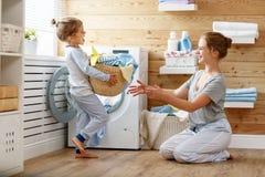 Lycklig familjmoderhemmafru och barn i tvätteri med washin Royaltyfria Foton