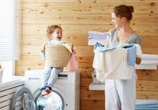 Lycklig familjmoderhemmafru och barn i tvätteri med washin Fotografering för Bildbyråer