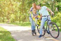 Lycklig familjridningcykel på parkera royaltyfri foto