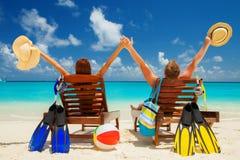Lycklig familjsemester på paradiset Par kopplar av på stranden royaltyfri fotografi