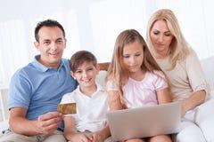 Lycklig familjshopping genom att använda bärbar dator Arkivbild