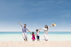 Lycklig familjspring på stranden Royaltyfri Foto