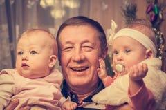 Lycklig familjstående av farfadern med hans barnbarn Arkivbild