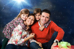 Lycklig familjstående med gåvor på jul Arkivbild