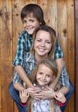 Lycklig familjstående mot träväggen Royaltyfri Fotografi