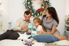 Lycklig familjstående på jul, modern, fadern och barnet som sitter på säng och tänder en stearinljus hemma, chritmas royaltyfri foto