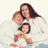 Lycklig familjstående - farmor, dotter och sondotter Arkivfoto
