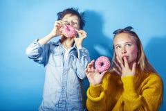 Lycklig familjsyskongrupp som ?ter donuts p? bl? bakgrund, ?ta f?r livsstilfolkbegrepp, f?r pojke och f?r flicka royaltyfri fotografi