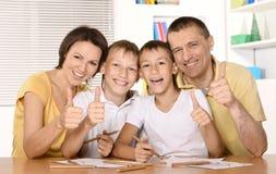 Lycklig familjteckning på tabellen tillsammans Arkivbild