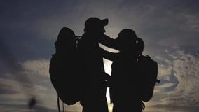 Lycklig familjturistkontur p? att kyssa f?r solnedg?ngkram teamworkloppbegrepp Man- och kvinnapar med ryggsäckar arkivfilmer