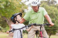 Lycklig farfar med hans sondotter på deras cykel Royaltyfri Foto