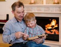 Lycklig farfar och barnbarn som läser en bok Royaltyfria Bilder