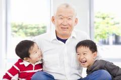 Lycklig farfar och barnbarn som tillsammans spelar Arkivbild
