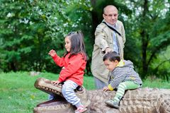 Lycklig farfar och små barnbarn som spelar i zoo Arkivbild
