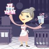 Lycklig farmor i köket med en födelsedag C Arkivfoton