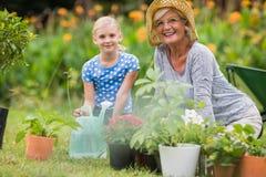 Lycklig farmor med hennes arbeta i trädgården för sondotter Arkivfoton