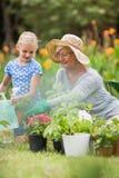 Lycklig farmor med hennes arbeta i trädgården för sondotter Arkivfoto
