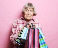 Lycklig farmor med shoppingpåsar över rosa bakgrund Livsstil och folkbegrepp arkivbilder