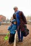 Lycklig farmor med sonsonen på lekplats Royaltyfria Foton