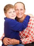Lycklig farmor som kramar 7 år sonson Arkivbilder
