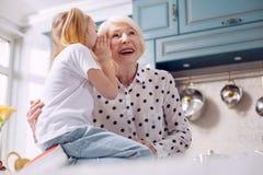 Lycklig farmor som lyssnar till hennes hemliga sondöttrar royaltyfria bilder