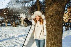 lycklig ferie Att spela för vinterkvinna kastar snöboll utomhus royaltyfria foton