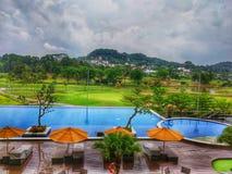 lycklig ferie med på den bästa semesterorten med simbassänger och golffältsikt royaltyfria bilder