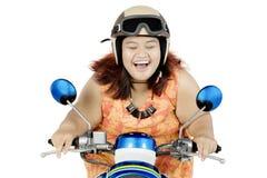 Lycklig fet kvinna som rider en motorcykel på studio Royaltyfri Foto