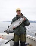 Lycklig fiskare i stor silverlax för håll Royaltyfria Bilder