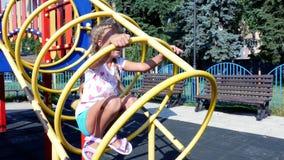 Lycklig flicka av sju år som spelar på lekplats och att ha gyckel på varm sommardag långsam rörelse Glad aktiv barndom arkivfilmer