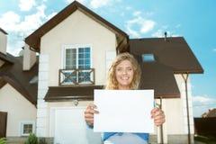 Lycklig flicka bredvid hennes nya hus Arkivbild