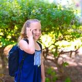 Lycklig flicka för litet barn att gå till skola och att tala på mobiltelefonen på staden för att parkera royaltyfri foto