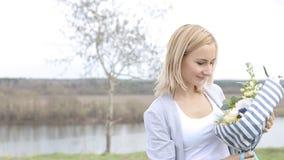 Lycklig flicka för skönhet med lockigt blont hår som luktar lösa blommor och att le arkivfilmer
