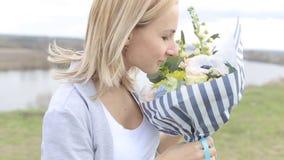 Lycklig flicka för skönhet med lockigt blont hår som luktar lösa blommor och att le lager videofilmer