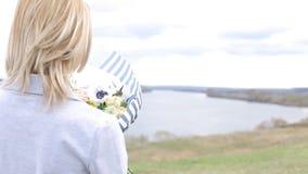 Lycklig flicka för skönhet med lockigt blont hår som luktar lösa blommor och att le stock video