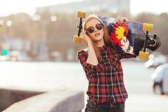 Lycklig flicka för sport som poserar i sommar med skateboarden Stilfull lycklig hipsterkvinna med färgrik longboard i solnedgång  Arkivfoto